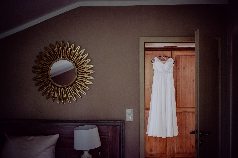 Brautkleid hängt an einem Bügel beim getting ready, Ausschnitt aus der Hochzeitsreportage fotografiert von Chris Hartlmaier Fotodesign