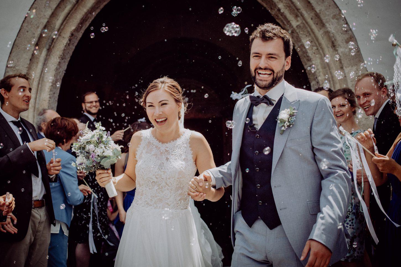 Auszug des Brautpaares aus der Kirche mit Seifenblasen, fotografiert von Chris Hartlmaier Fotodesign